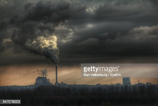 Factory Emitting Smoke Against Cloudy Sky