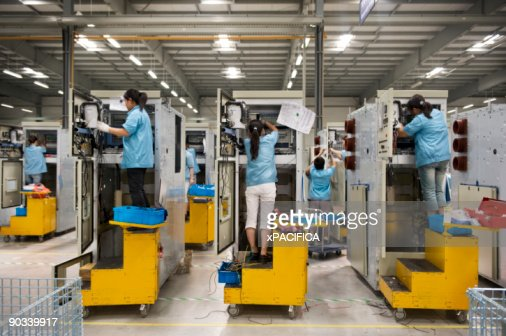 Factory employees wiring machinery.  : Stock Photo