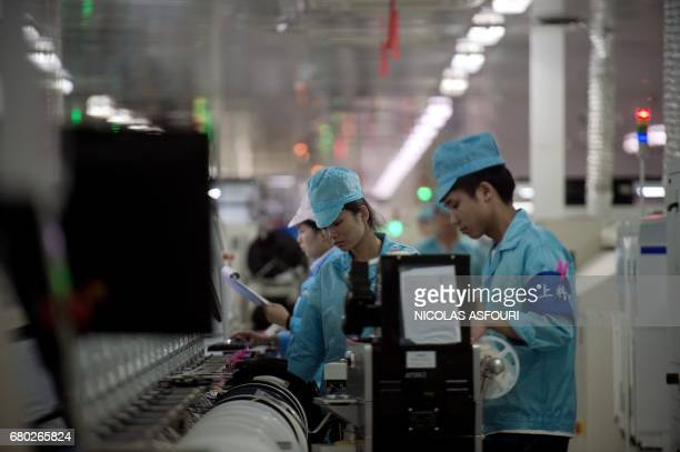 Factory employees work at the main factory of Chinese smartphone maker Oppo in Dongguan on May 8 2017 Chinese exports rose for the second consecutive...
