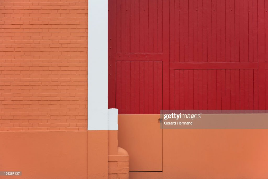 CONTENT] A factory entrance recently painted with art in red, beige and white. On the left: a brick wall. At the center of the photo: a little door (for workers) included in the huge portal.