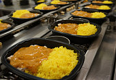 Individual portion curry and rice ready-meals being manufactured in a high speed food factory process