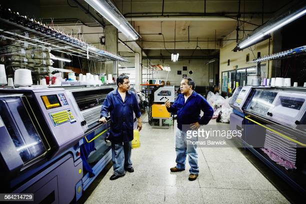 Factory manager in discussion with coworker
