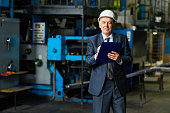Portrait of smiling senior businessman wearing hardhat looking at camera holding clipboard in workshop of modern factory