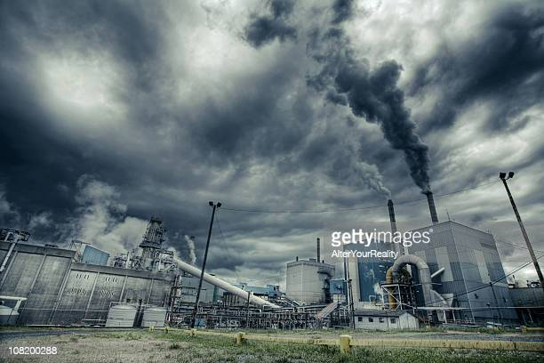 Factory smoke polluting air in a cloudy day