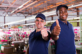 cheerful factory supervisors giving thumbs up