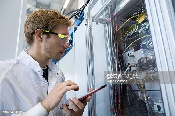 Factory technician inspecting equipment using digital tablet
