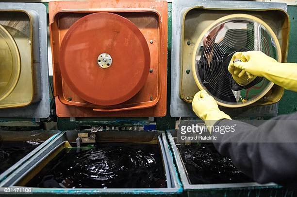 Factory worker Arek Grzeda places a master copy of a vinyl record in place ready to be submerged into nickel plating solution before being ready to...
