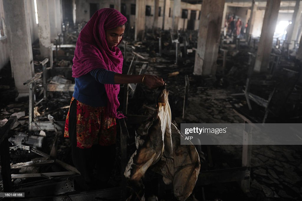 Factory worker Bangladeshi Shahinur looks though the devastation after a fire swept though the garment factory in Dhaka on January 27, 2013. At least seven female workers were killed on January 26 after a blaze swept through a small garment factory in the Bangladeshi capital of Dhaka, police and fire officials said. AFP PHOTO / Munir uz ZAMAN