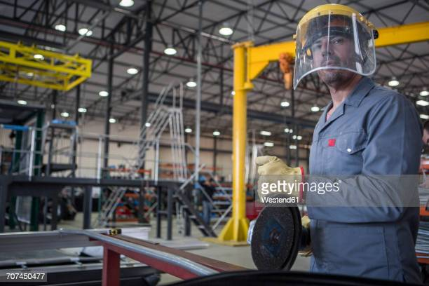 Factory worker in truck manufacture using buzz saw