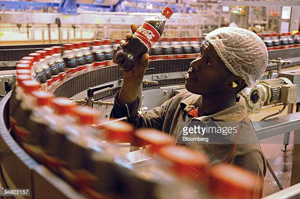 A factory worker inspects a bottle at the Coca Cola bottling plant operated by Amalgamated Beverage Industries Limited the soft drink division of SAB...