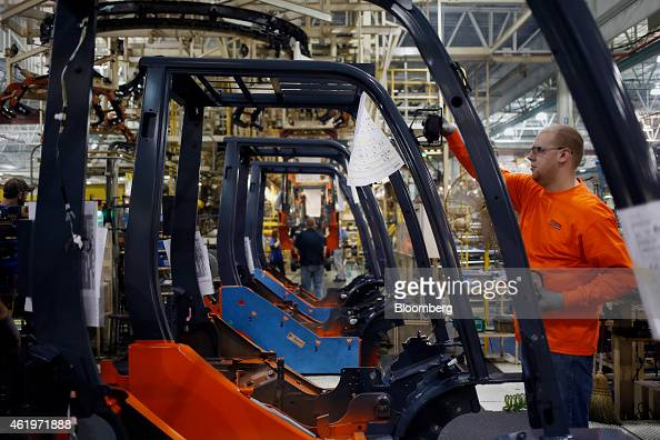 A factory worker installs components for a forklift on the assembly line at the Toyota Industrial Equipment Manufacturing Inc facility in Columbus...