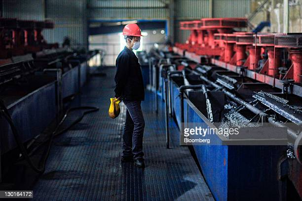 A factory worker looks over machines processing silver zinc and lead ore at the Silvercorp Metals Inc mill in Jiyuan Henan Province China on Tuesday...