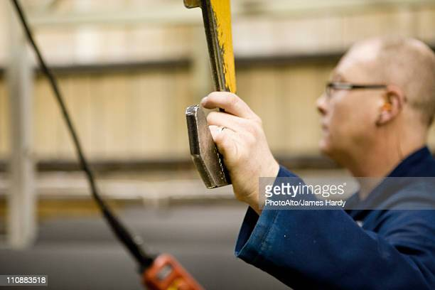 Factory worker operating lift in carpet tile factory