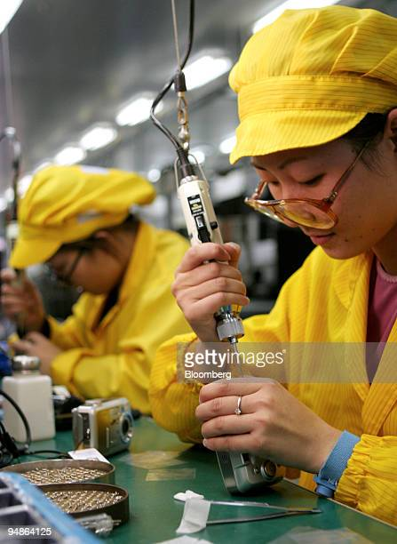 A factory worker performs quality control work on a Kodak digital camera on a production line in Shanghai China December 10 2004 China's industrial...