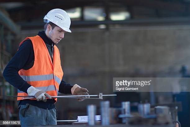 Factory worker selecting metal rod in concrete reinforcement factory
