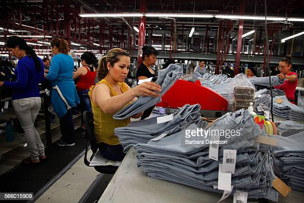 A factory worker uses an Avery fastener machine to attach Point of Sales price tickets/tags to the garments April 11 2013 This story is for profile...