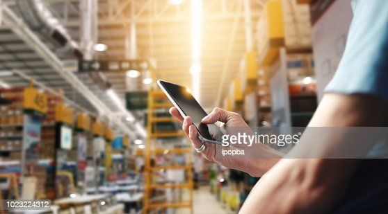 Factory worker using application on mobile smartphone to operate automation for modern trade. Checking order in large warehouse. Import and export the shipping cargo. : Foto stock