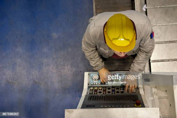 Factory worker using computer to operate automation