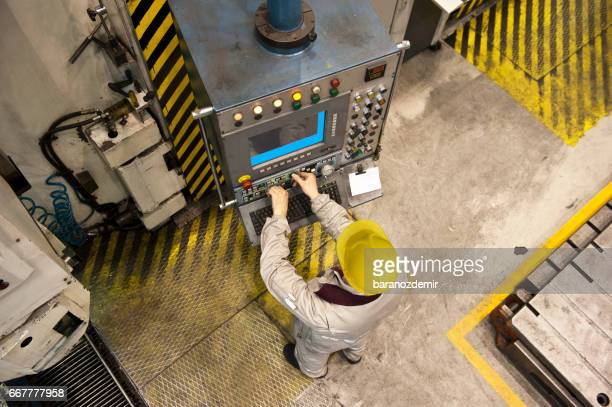 Factory worker using computer to operate machine