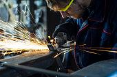 Worker grinding a metal part in his workshop.