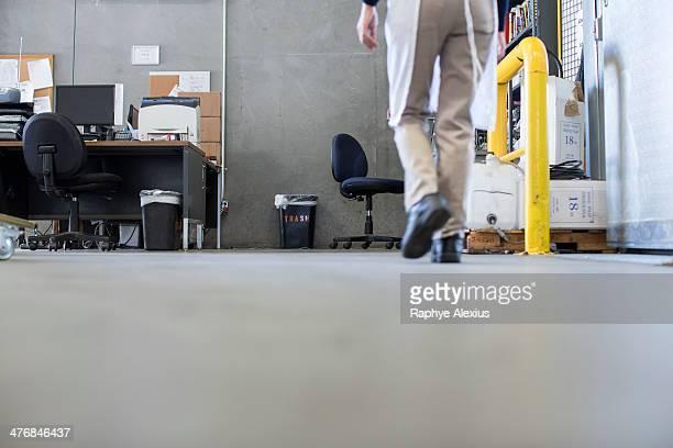 Factory worker walking along floor, low section