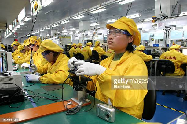 Factory workers assemble Kodak digital camera on a production line in Shanghai China December 10 2004