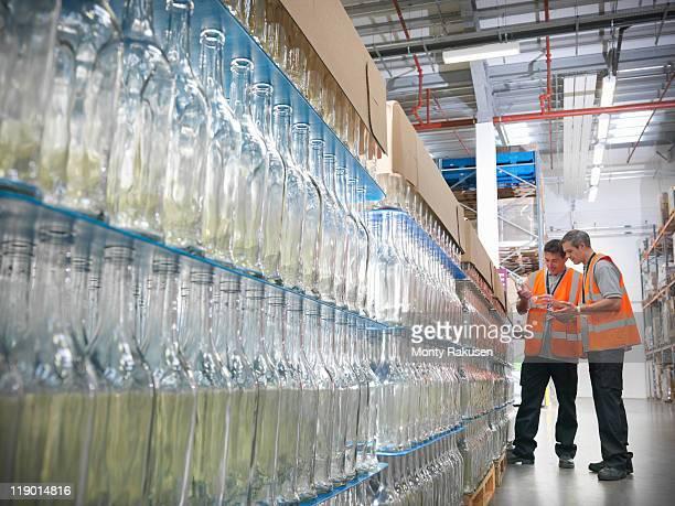 Factory workers examining bottles