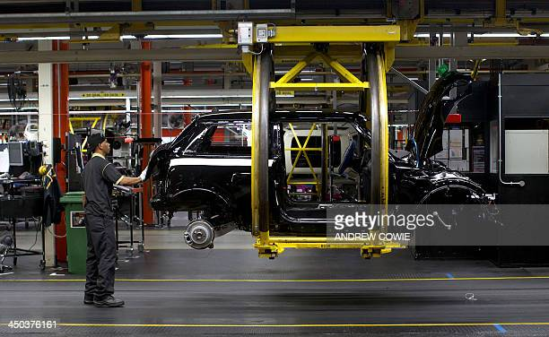 Factory workers produce Mini cars at the BMW's plant at Cowley in Oxford central England on November 18 2013 Car giant BMW which has been...