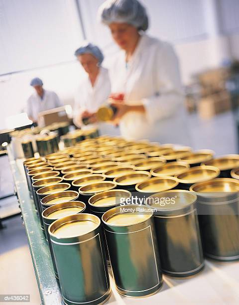 Factory workers putting labels on cans