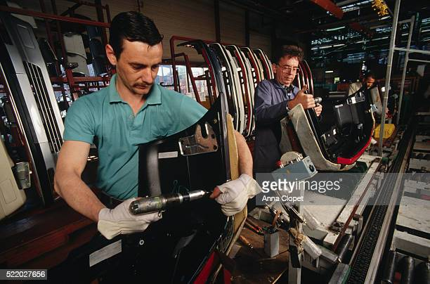 Factory Workers Putting Together Automobile Parts