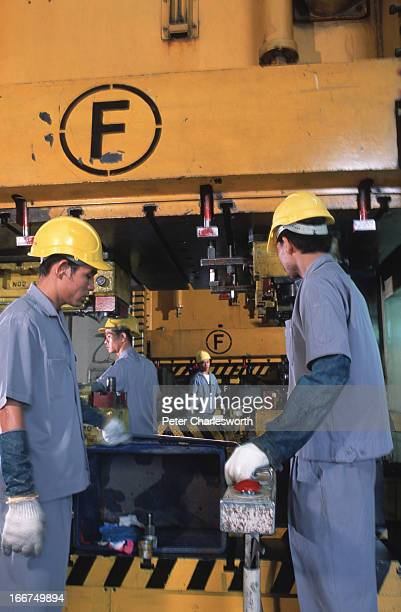 Factory workers use 500 ton stampingpress machines to stamp plates and panels for car parts at the Aapico Hitech Public Company Limited factory The...