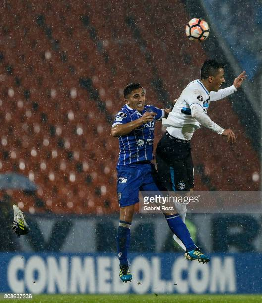 Facundo Cobos of Godoy Cruz fights for the ball with Lucas Barrios of Gremio during a first leg match between Godoy Cruz and Gremio as part of round...