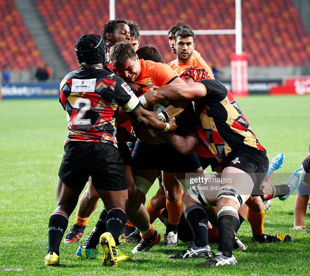 Facundo Isa (C) of the Jaguares is tackled during the Super Rugby clash between Kings and Jaguares at the Nelson Mandela Bay rugby stadium on May 27, 2016 in Port Elizabeth. / AFP / MICHAEL