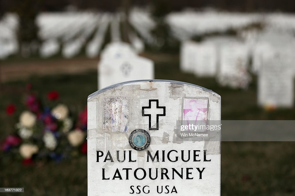 Faded photographs cover the top of the headstone at the grave of Staff Sergeant Paul M. Latourney, of Roselle, Illinois in Section 60 at Arlington National Cemetery March 15, 2013 in Arlington, Virginia. Section 60 is the section of the cemetery where American military members killed in Iraq and Afghanistan are currently laid to rest, though soldiers and Marines from World War II through Afghanistan are also buried in the section. March 20th marks the ten-year anniversary of the beginning of the war in Iraq. Latourney was kiiled when an improvised explosive device detonated near his vehicle while on combat patrol in Iraq.