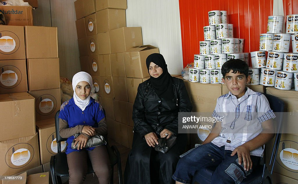 HASNI - Fadia, a Syrian refugee wife and mother of Syrian rebels, sit near her son Mohamad and daughter Nagham at a charity centre, shortly after they crossed the Lebanese border with Syria on September 4, 2013 in Masnaa. Fadia refused to leave her war-torn country until the very last minute despite the violence ravaging her home city, the capital Damascus but she finally made the decision to go, pushed by her son who feared for her safety if the United States decided to launch military strikes against the regime. The charity center belongs to a Lebanese charity financed by Qatari benefactors.