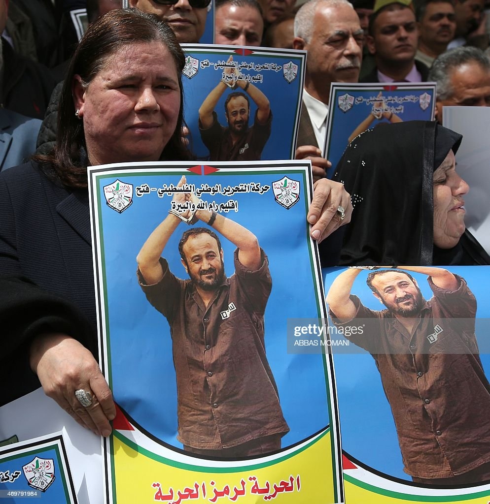 Fadwa Barghuti (L), the wife of jailed Palestinian Fatah leader Marwan Barghuti, holds a placard bearing his portrait, during a march to mark the anniversary of his arrest and the demand of his release from Israeli prison, in the West Bank city of Ramallah on April 15, 2015. Barghuti was sentenced to life imprisonment in 2002 for organizing anti-Israeli attacks during the Second Intifada in 2000