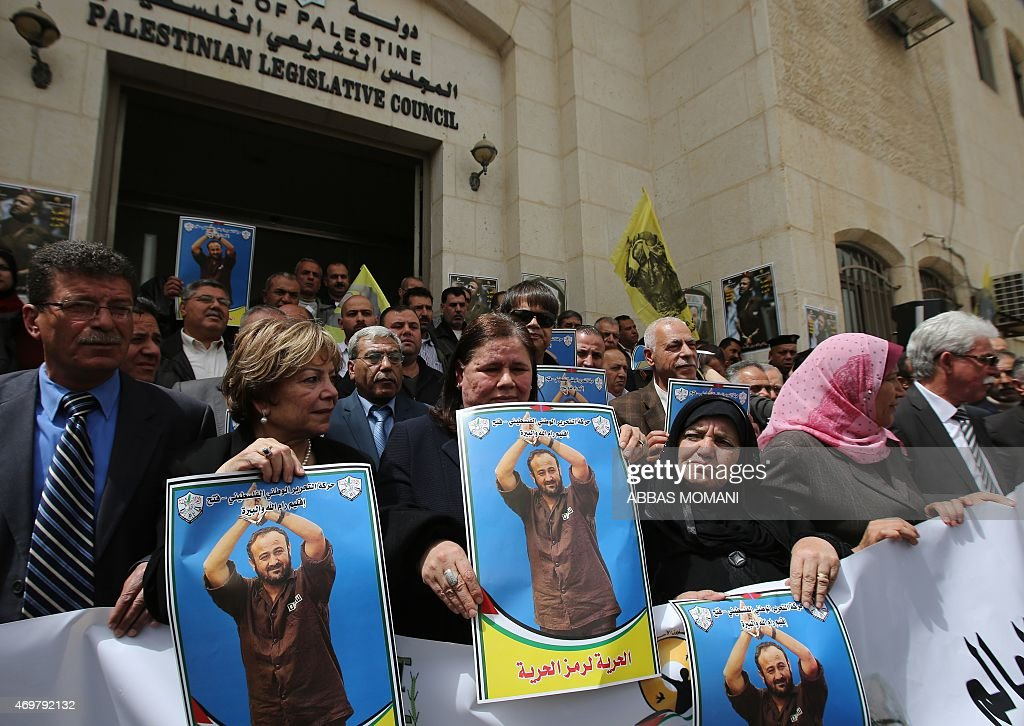 Fadwa Barghuti (C), the wife of jailed Palestinian Fatah leader Marwan Barghuti, holds a placard bearing his portrait, during a march to mark the anniversary of his arrest and demand his release from Israeli prison, in the West Bank city of Ramallah on April 15, 2015. Barghuti was sentenced to life imprisonment in 2002 for organizing anti-Israeli attacks during the Second Intifada in 2000.