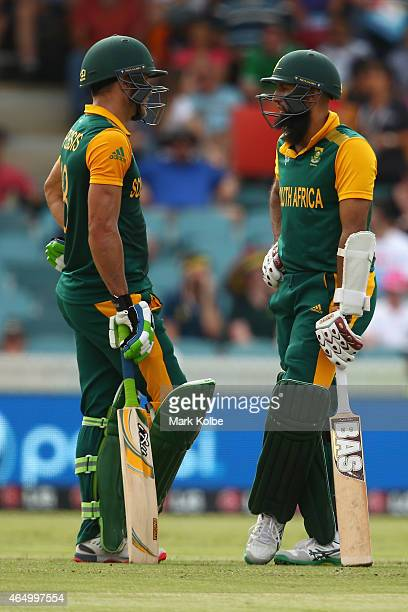 Faf du Plessis and Hashim Amla of South Africa speak as they bat during the 2015 ICC Cricket World Cup match between South Africa and Ireland at...