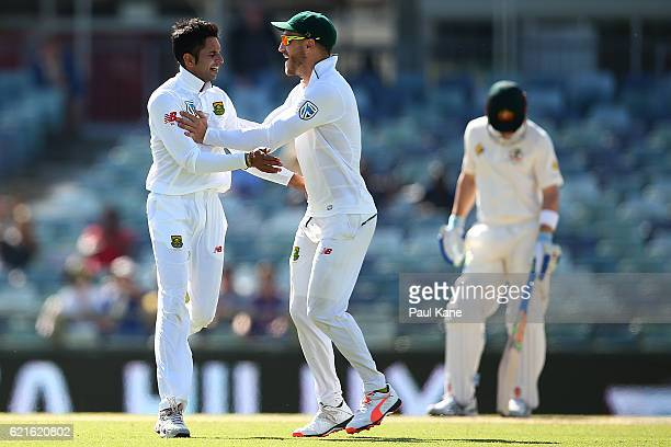 Faf du Plessis and Keshav Maharaj of South Africa celebrate after defeating Australia during day five of the First Test match between Australia and...