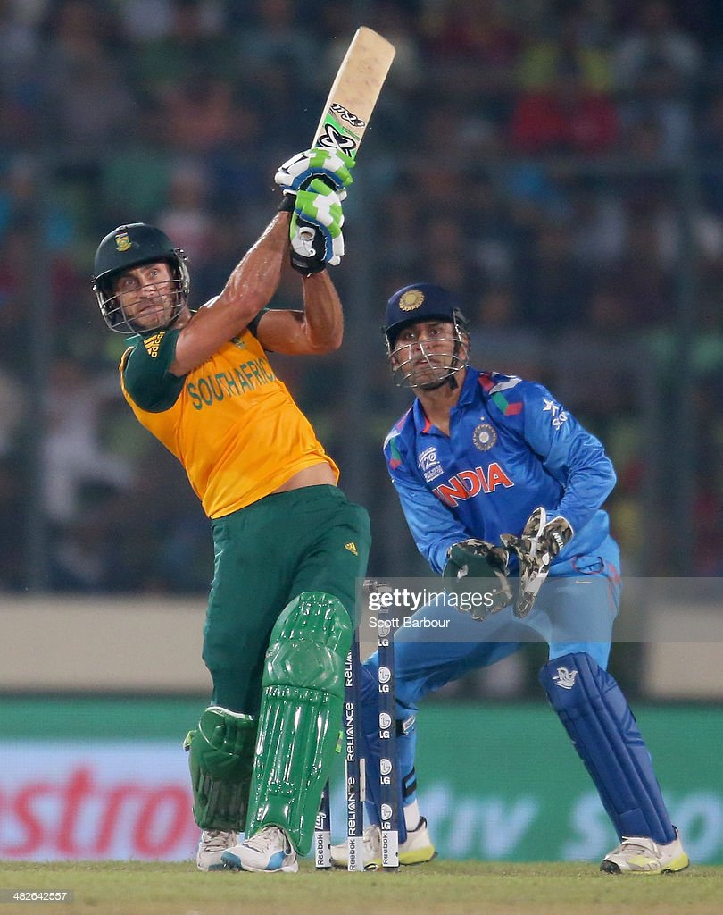 Faf du Plessis of South Africa hits a boundary as MS Dhoni of India looks on during the ICC World Twenty20 Bangladesh 2014 2nd Semi-Final match between India and South Africa at Sher-e-Bangla Mirpur Stadium on April 4, 2014 in Dhaka, Bangladesh.