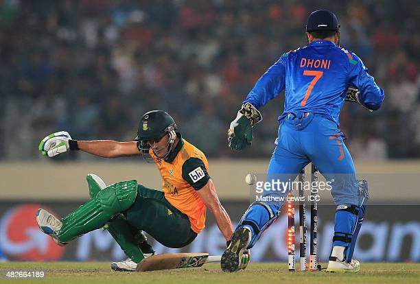 Faf du Plessis of South Africa is bowled by Ravichandran Ashwin of India as MS Dhoni looks on during the ICC World Twenty20 Bangladesh 2014 Semi...