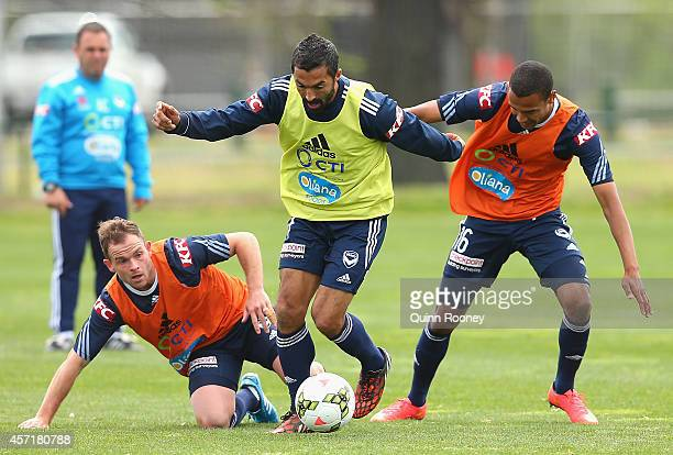 Fahid Ben Khalfallah of the Victory is tackled by Leigh Broxham and Rashid Mahazi during a Melbourne Victory Training Session at Gosch's Paddock on...