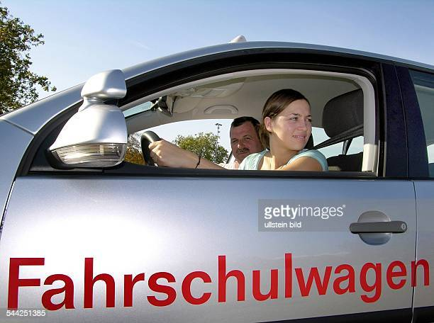 Fahrschule Junge Frau beim Einparken mit dem Fahrschulauto