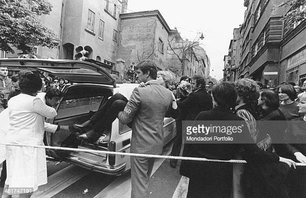 A fainted young woman being carried toward an ambulance at the funerals of the President of the Socialist Federal Republic of Yugoslavia Josip Broz...