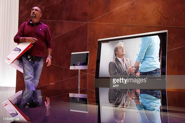 A fair goer walks past Loewe televisions during the IFA consumer electronic fair in Berlin on September 2 2011 The IFA consumer electronics fair is...