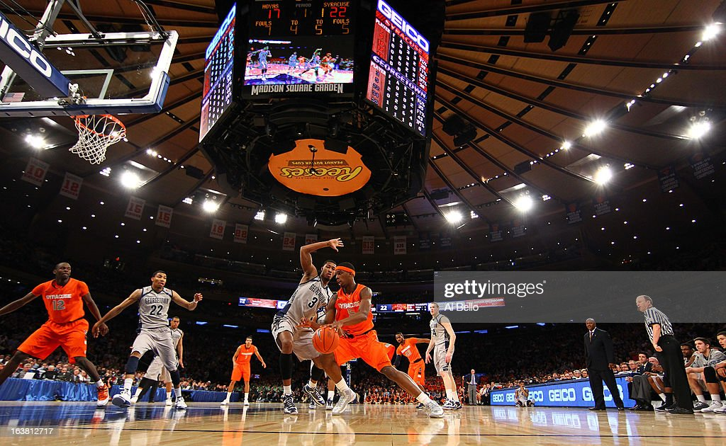 C.J. Fair #5 of the Syracuse Orange drives against Mikael Hopkins #3 of the Georgetown Hoyas during the semifinals of the Big East Men's Basketball Tournament at Madison Square Garden on March 15, 2013 in New York City.
