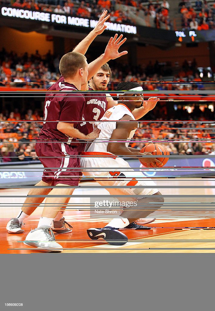 C.J. Fair #5 of the Syracuse Orange drives to the basket against Pat Moore #5 and John Brandenburg #3 of the Colgate Raiders during the game at the Carrier Dome on November 25, 2012 in Syracuse, New York.