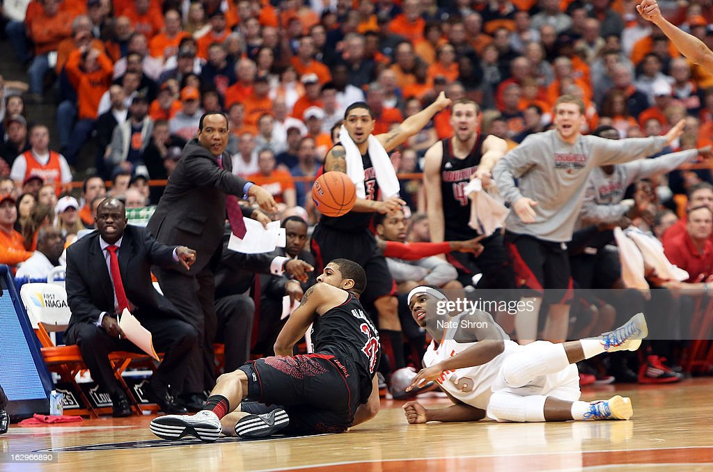 C.J. Fair #5 of the Syracuse Orange falls to the ground reaching for the ball against Chane Behanan #21 of the Louisville Cardinals as players react on the bench during the game at the Carrier Dome on March 2, 2013 in Syracuse, New York.
