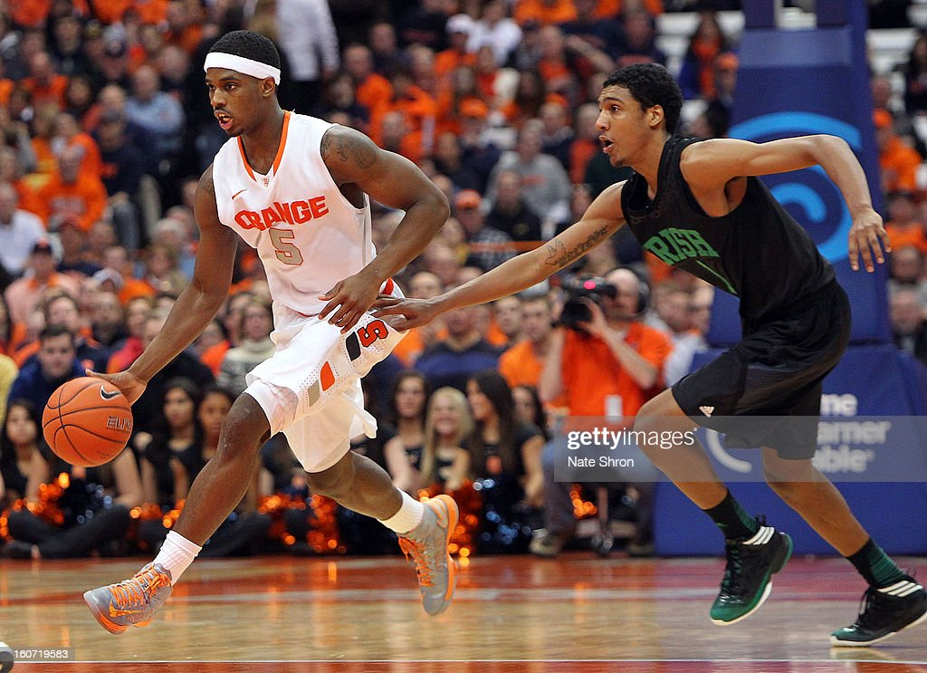 C.J. Fair #5 of the Syracuse Orange takes the ball down the court against Cameron Biedscheid #1 of the Notre Dame Fighting Irish during the game at the Carrier Dome on February 4, 2013 in Syracuse, New York.