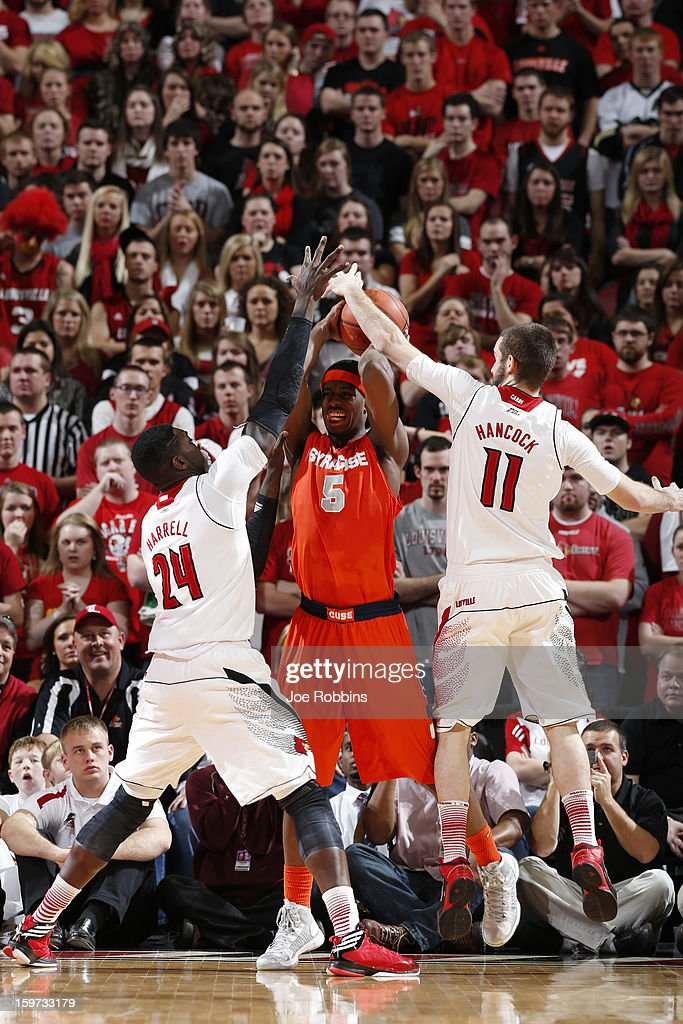 C.J. Fair #5 of the Syracuse Orange tries to pass the ball against pressure from Montrezl Harrell #24 and Luke Hancock #11 of the Louisville Cardinals during the game at KFC Yum! Center on January 19, 2013 in Louisville, Kentucky. Syracuse defeated Louisville 70-68.